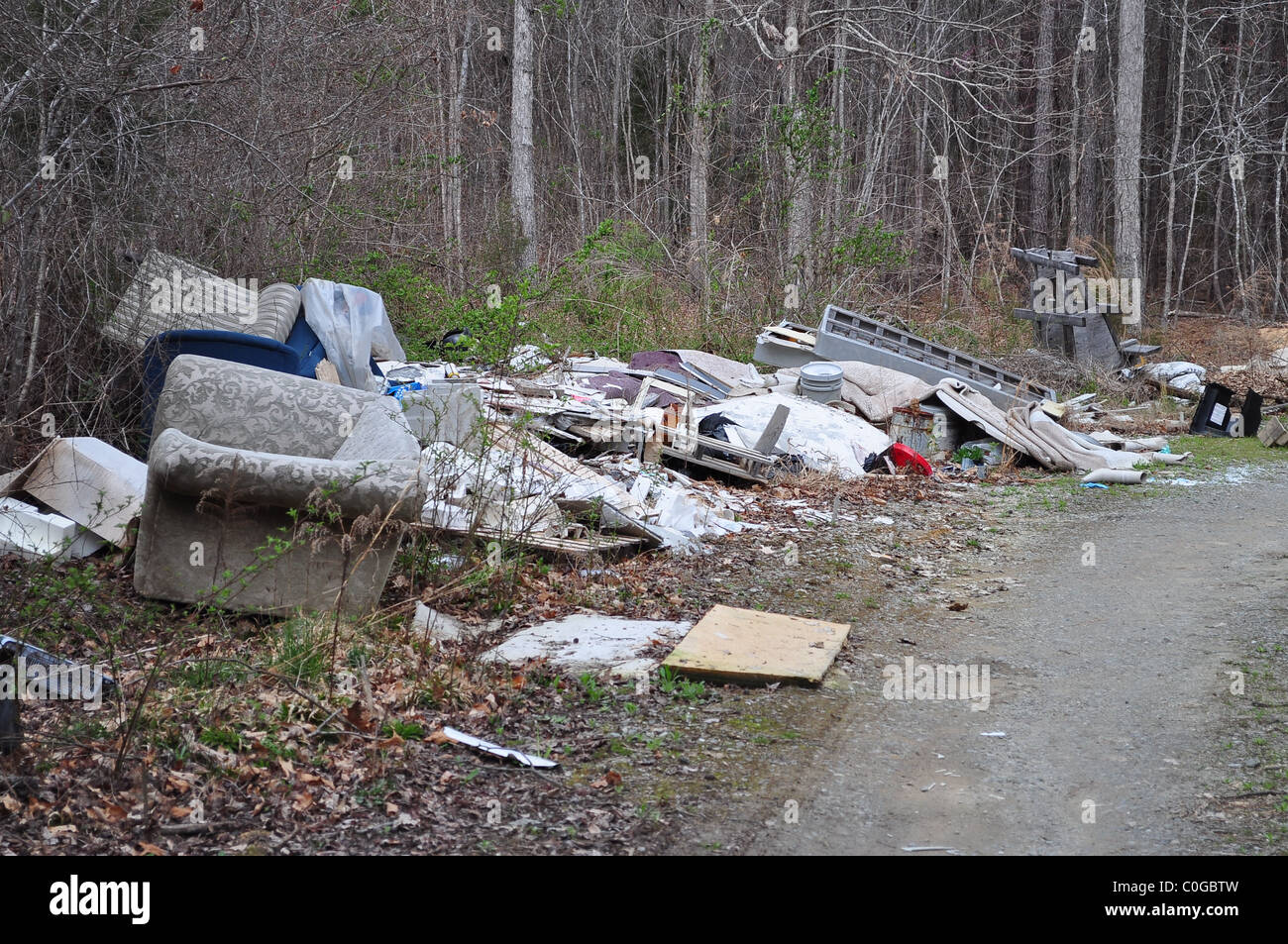 Junk and trash dumped on a rural road. - Stock Image