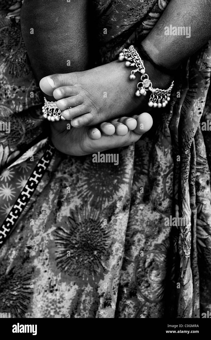 Indian babies bare feet against mothers floral sari. Monochrome - Stock Image
