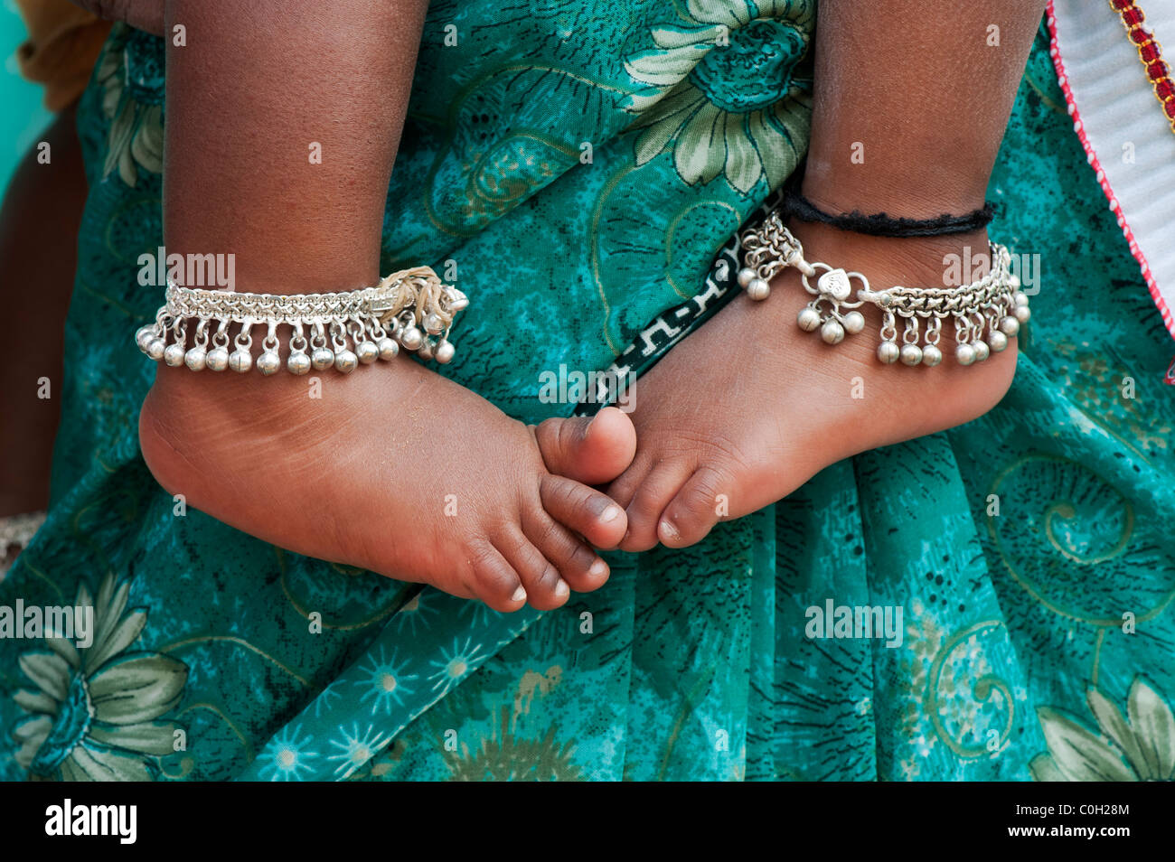 Indian babies bare feet against mothers green floral sari. Andhra Pradesh, India - Stock Image