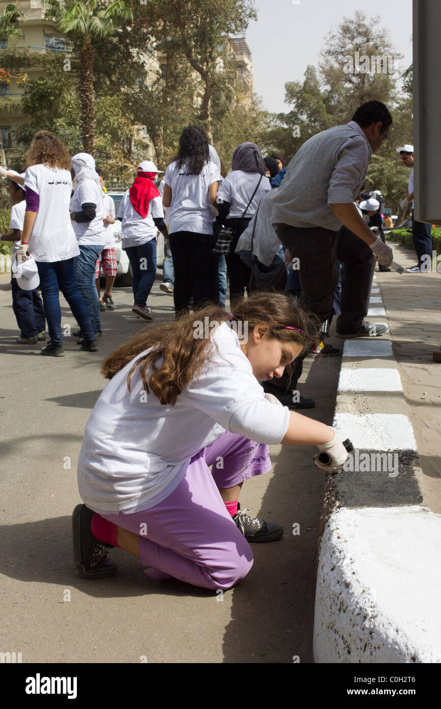 Egyptian schoolchildren painting curbstones in cleanup operation in Maadi, suburb of Cairo, Egypt - Stock Image