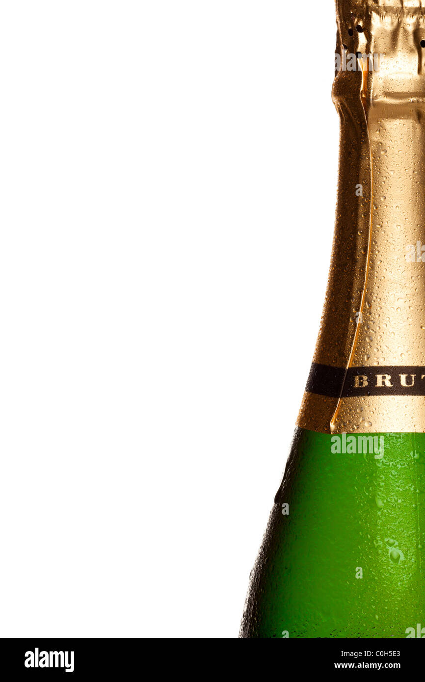 Close up photo of champagne bottle covered in water droplets, on right side of frame with white background. - Stock Image