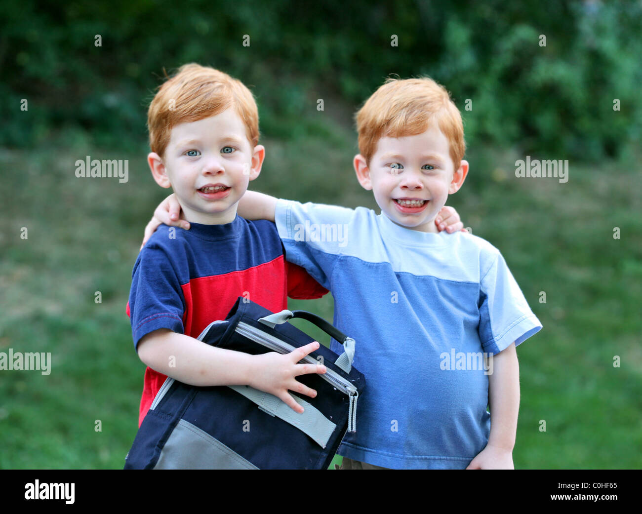 Twin boys with arms around each other outside portrait - Stock Image
