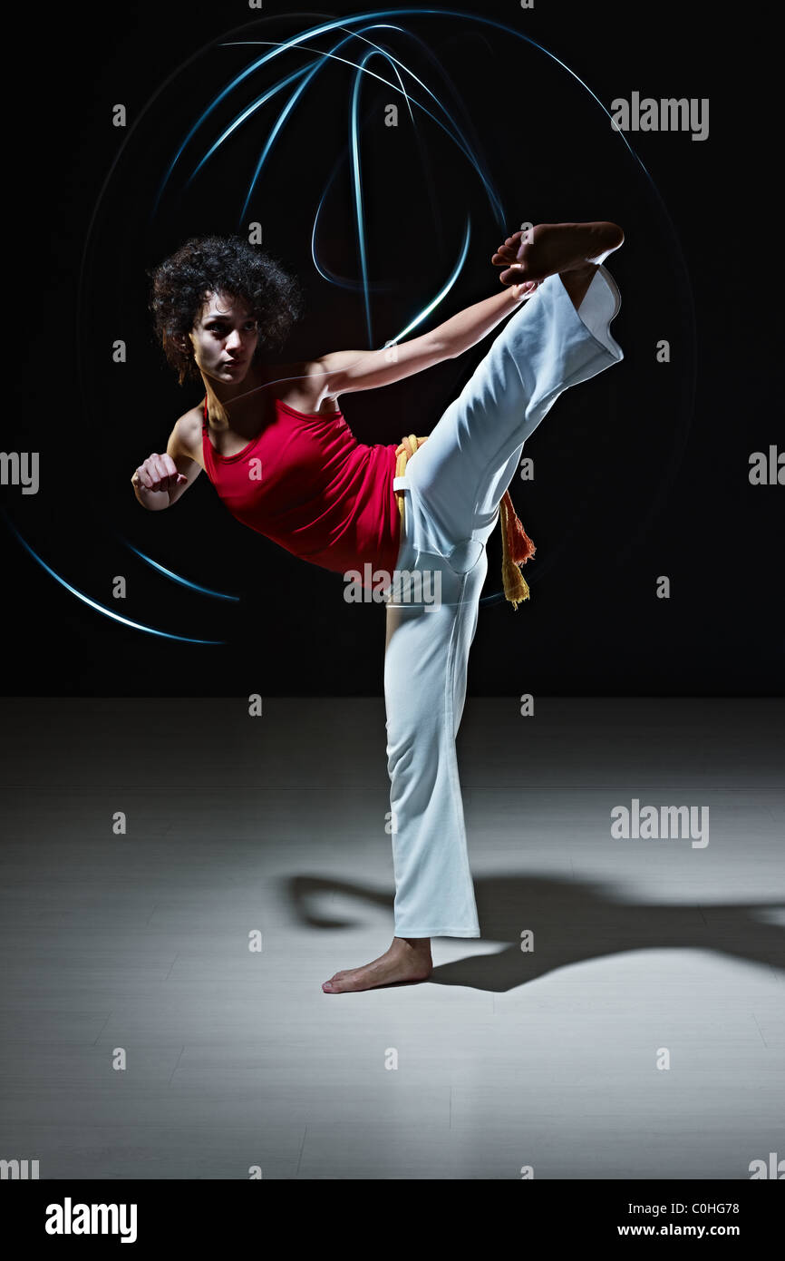 young adult latin american female doing capoeira side kick in gym, with streaks of led lights on top. Stock Photo