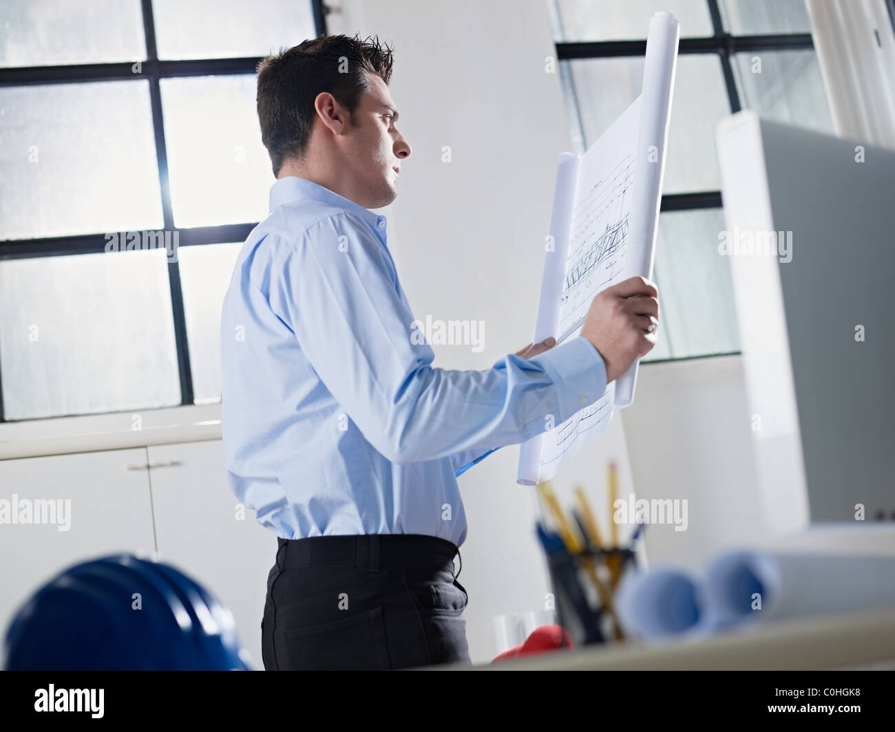 mid adult caucasian male architect examining building plan. Horizontal shape, waist up, side view - Stock Image