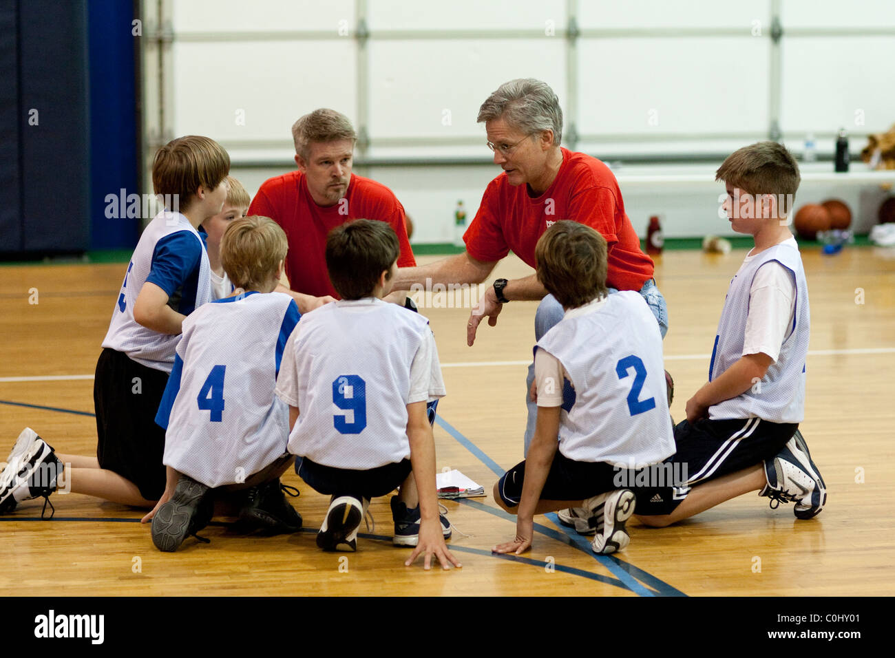 Volunteer coaches instruct 10-year-old boys during practice for youth-league basketball team at gym in Austin Texas - Stock Image