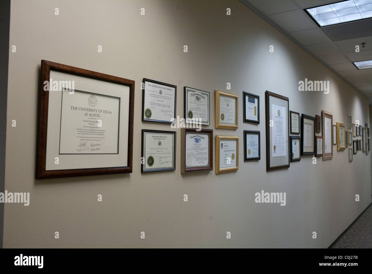 Framed diplomas, degrees, certificates and awards earned by attorneys line wall of law firm's office in Austin - Stock Image