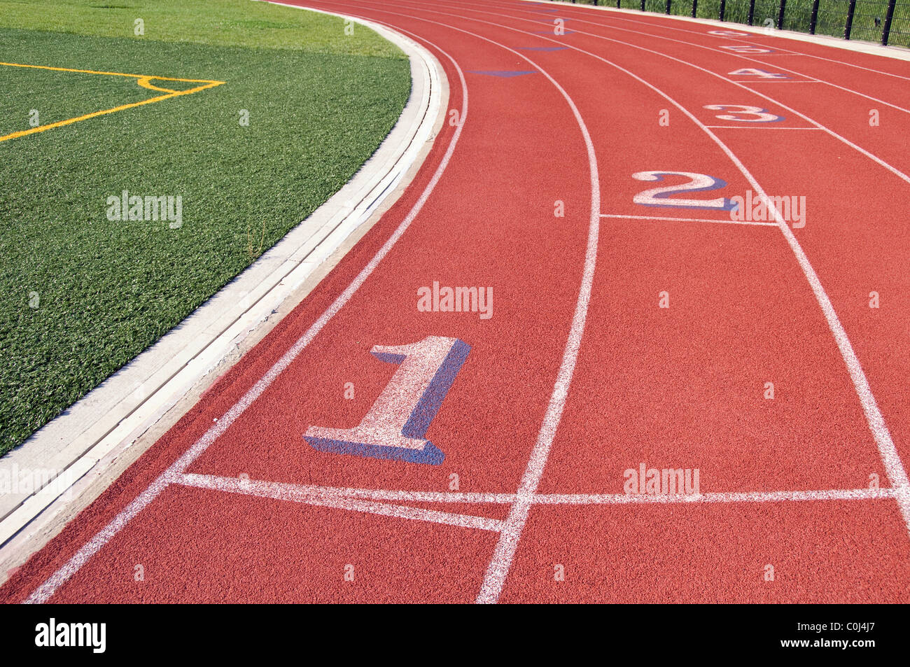 Lanes of a red race track with numbers and green football field Stock Photo