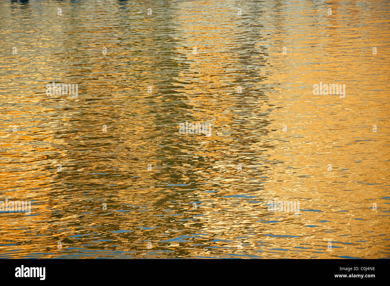 golden ripple water reflections - Stock Image
