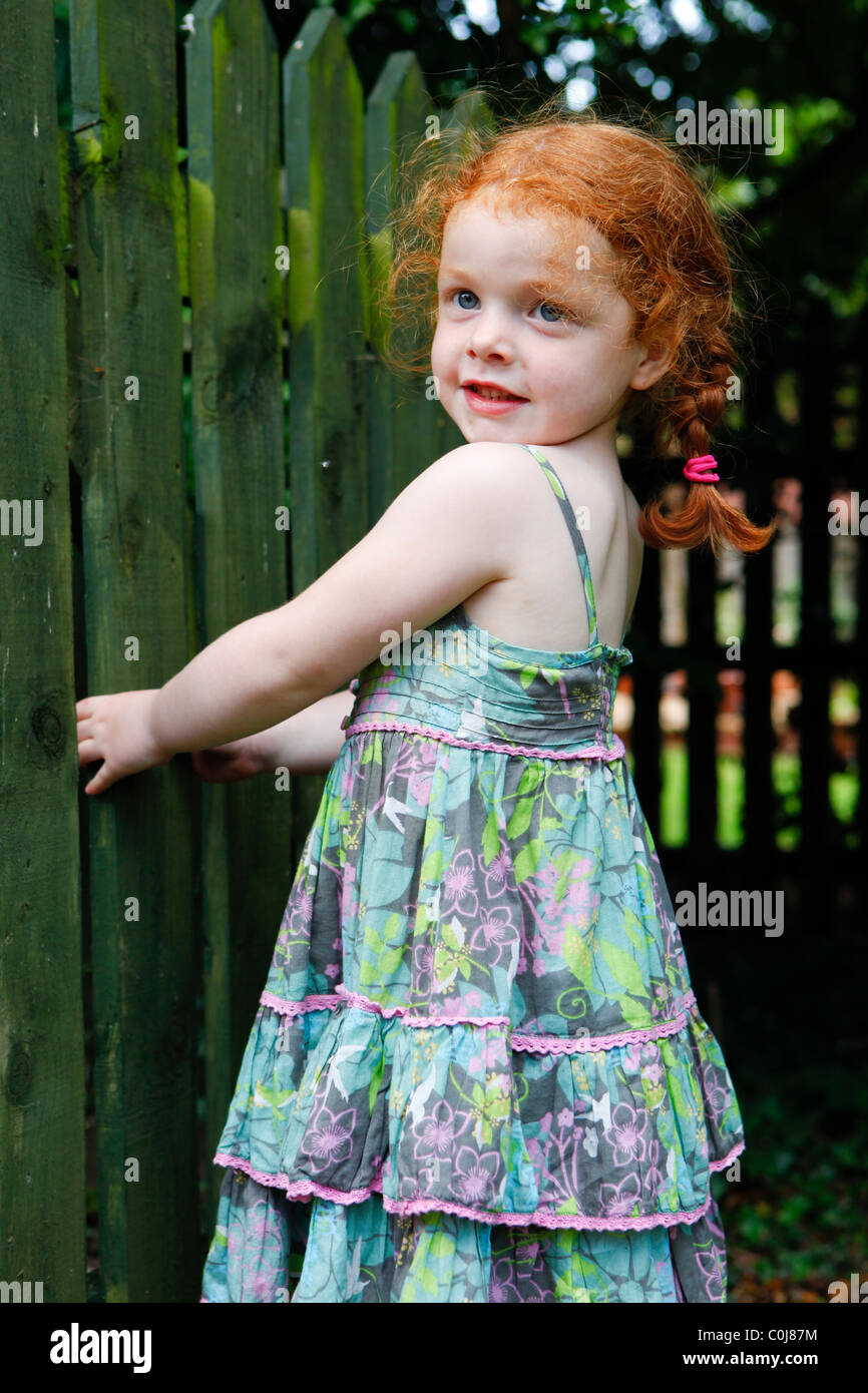 Four year old girl in her garden with plaits. Playing on a gate. - Stock Image
