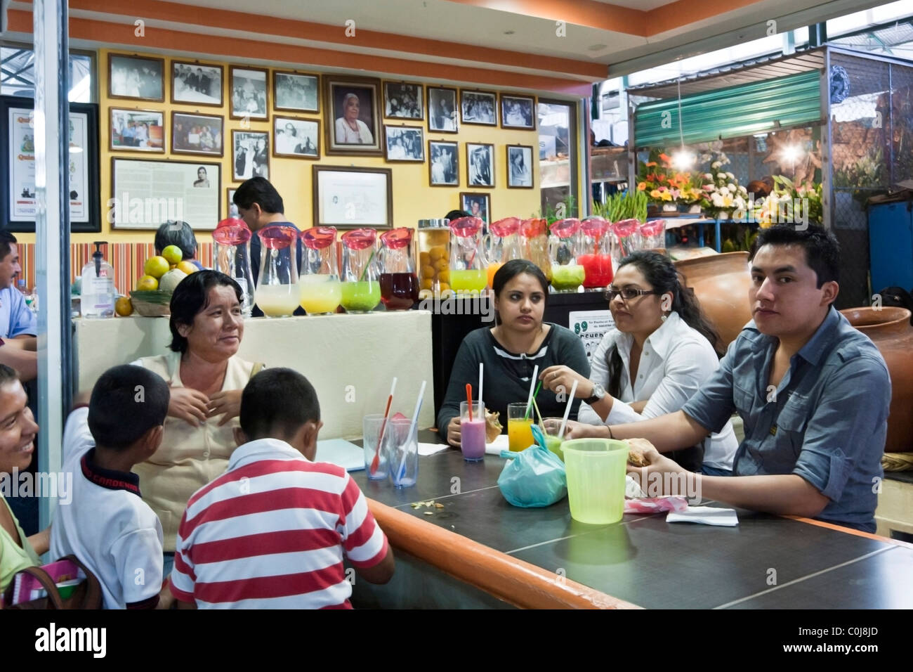 family group at a table in old restaurant inside Benito Juarez market Oaxaca City Mexico - Stock Image