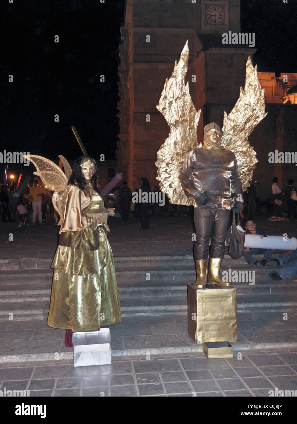 man & woman beautiful shimmering golden angel mime fortune  tellers holding bag & box of destinies at night - Stock Image