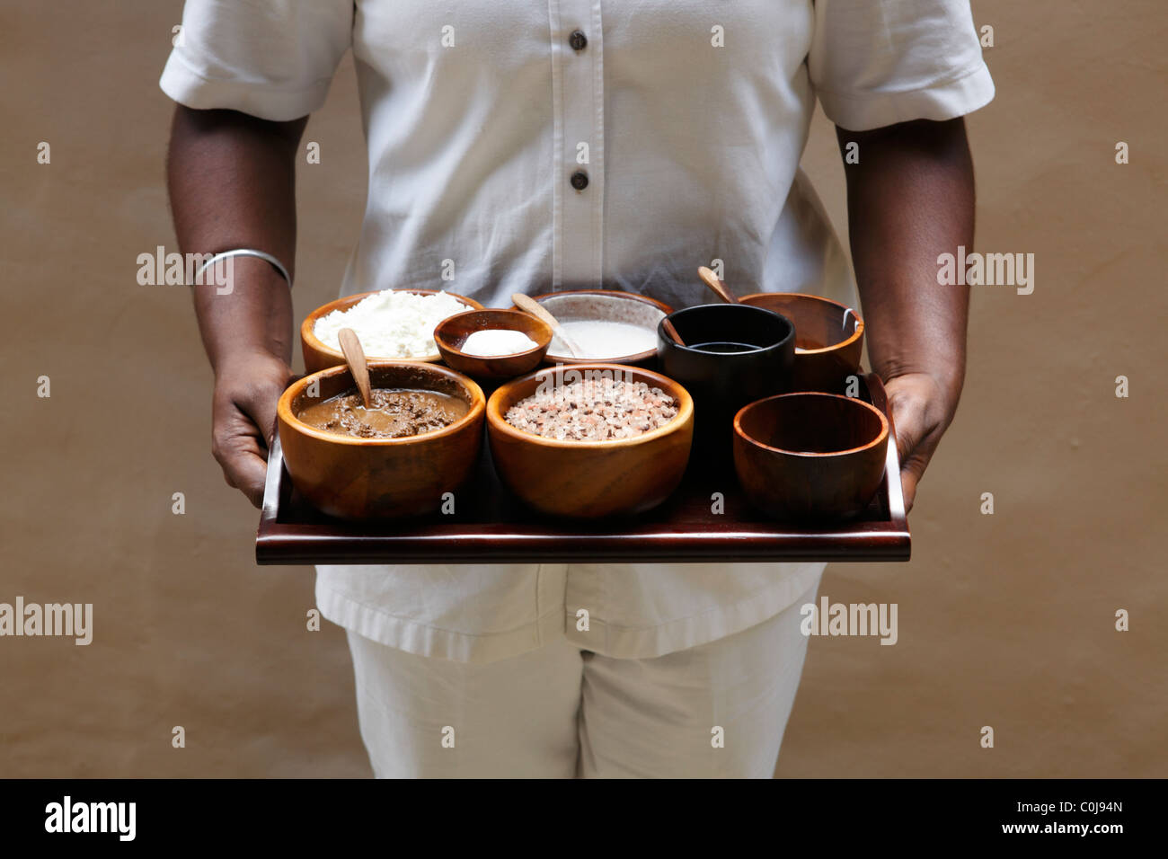 Spa therapist displays ingredients for traditional Malay treatment - Stock Image