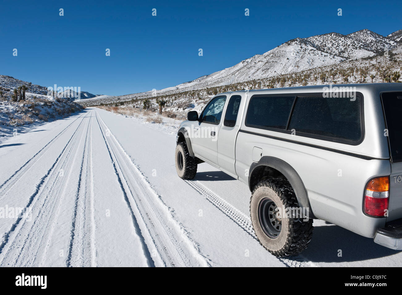 4 wheel drive truck on Snow covered high desert road, Death Valley national park, California - Stock Image