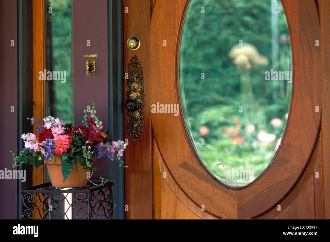 WOOD FRONT ENTRANCE DOOR TO AN AMERICAN HOME WITH OVAL GLASS MIRROR INSET AND POT OF ANNUALS.  U.S.A. - Stock Image