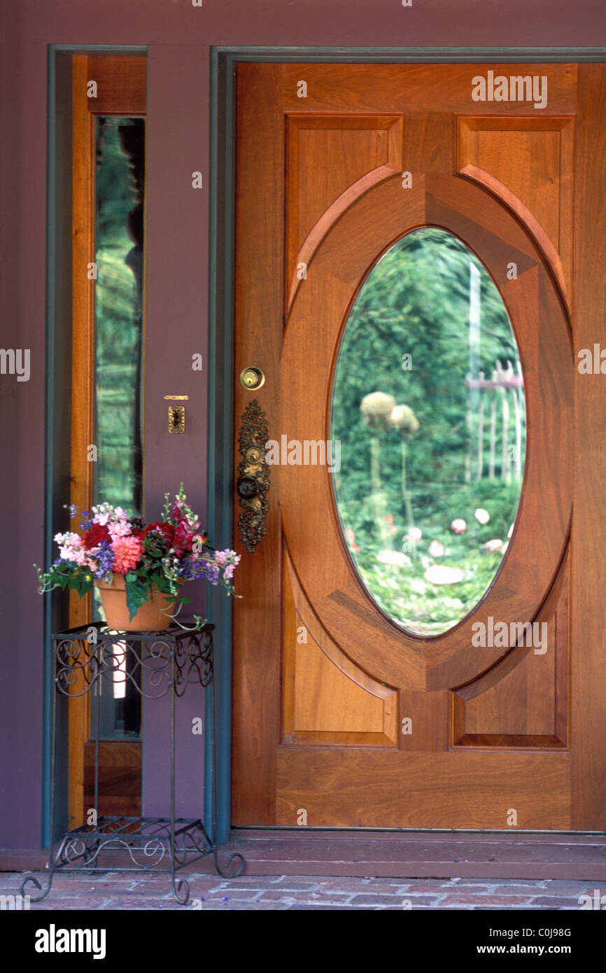WOOD FRONT ENTRANCE DOOR TO AN AMERICAN HOME WITH OVAL GLASS MIRROR INSET.  U.S.A. - Stock Image