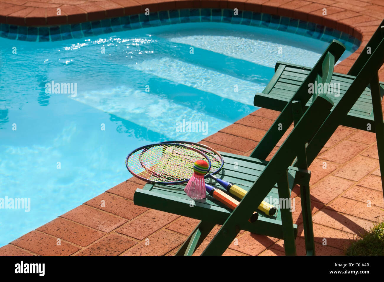 Two Deck Chairs And Garden Badminton Set Next To Swimming Pool.