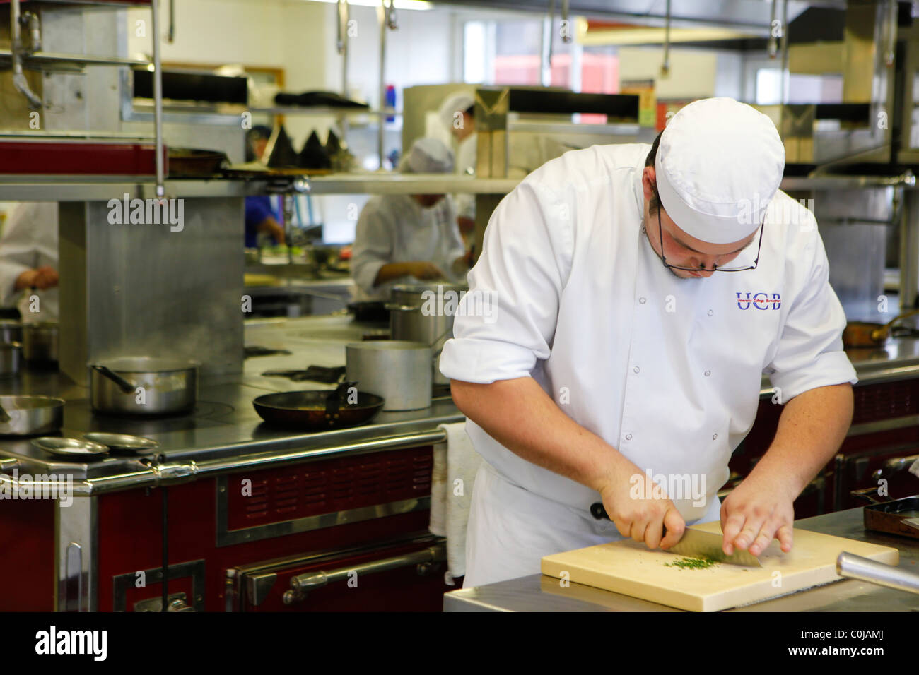 Chefs in a kitchen preparing food at a college for further and higher education - Stock Image