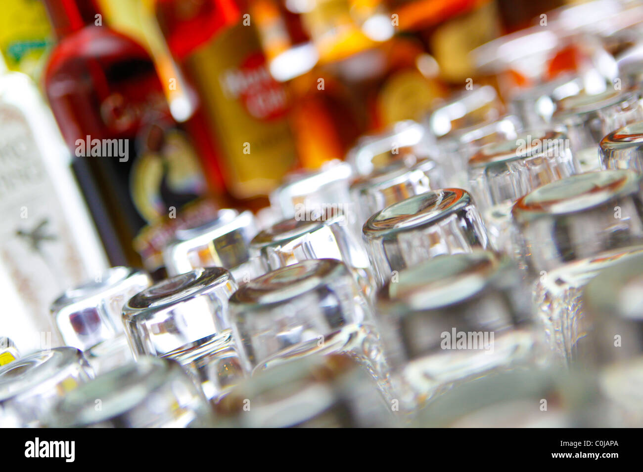 Glasses and bottles of alcohol on a bar - Stock Image