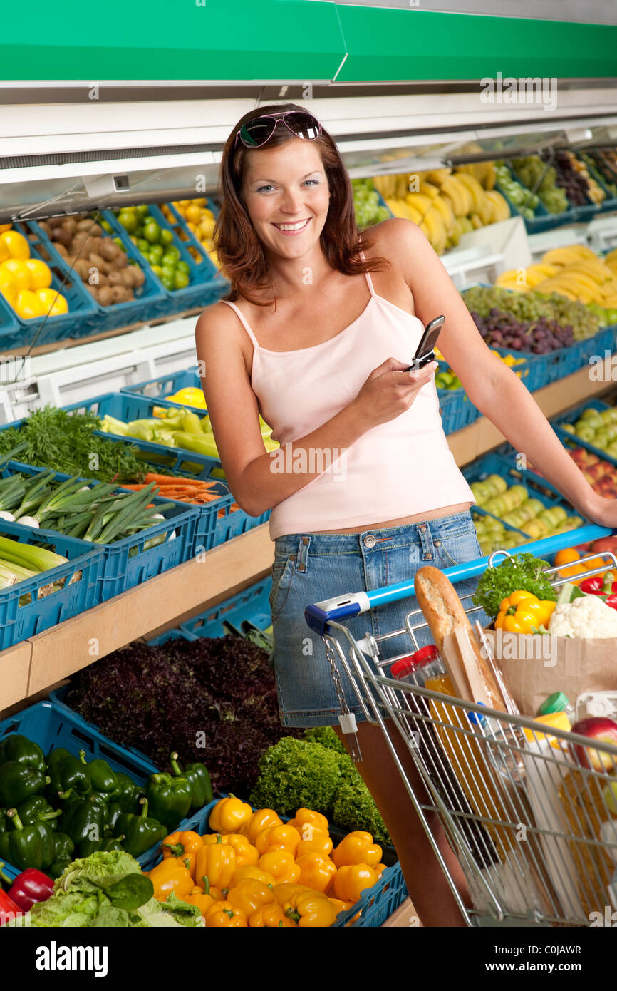 Grocery store shopping - Young woman with mobile phone in a supermarket - Stock Image
