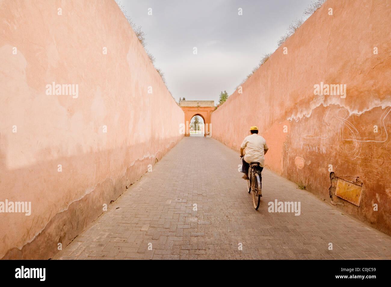 A man exiting the Marrakesh medina on a bicycle. Stock Photo