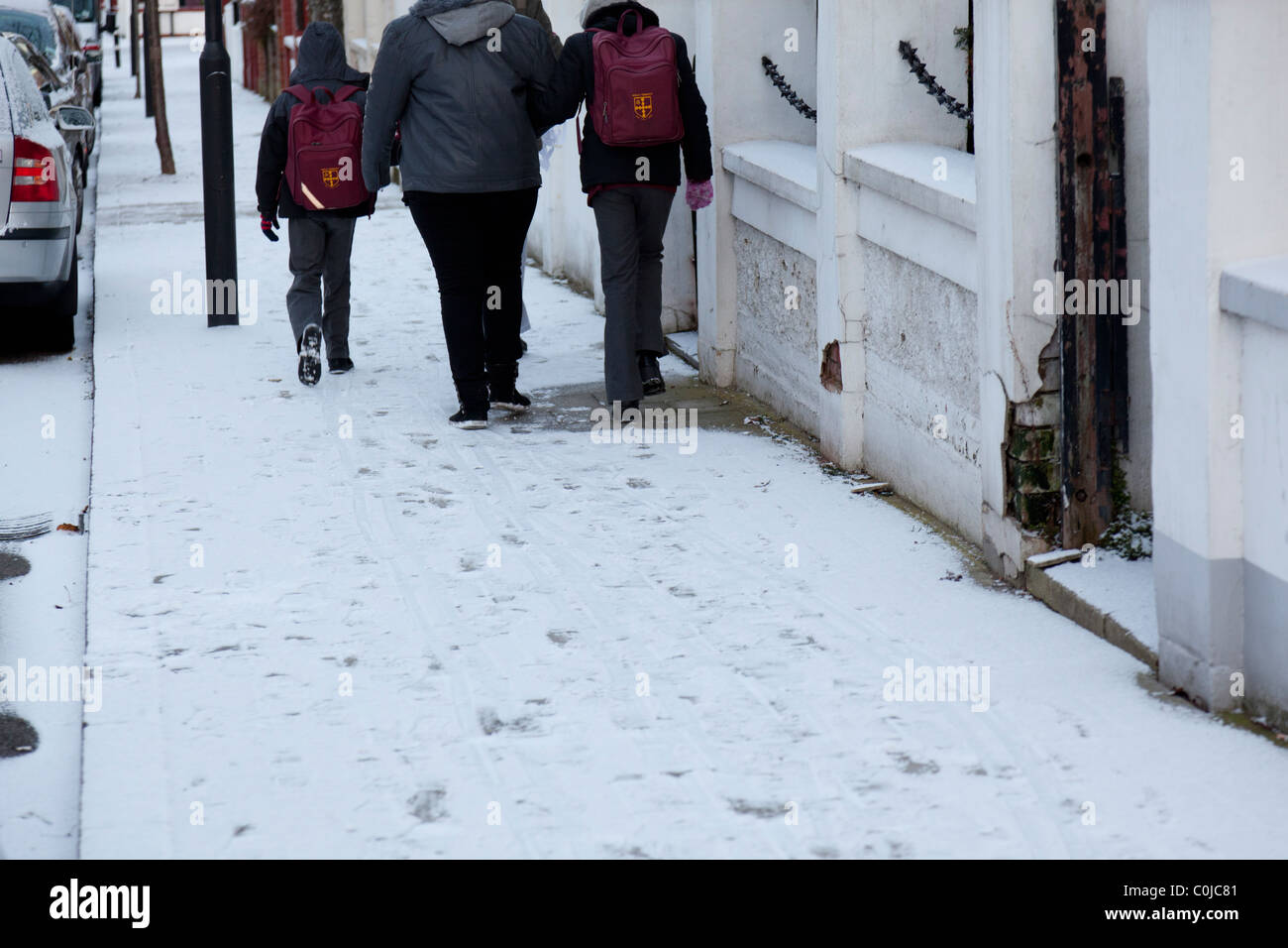 Mother and school children walking in snow covered street - Stock Image