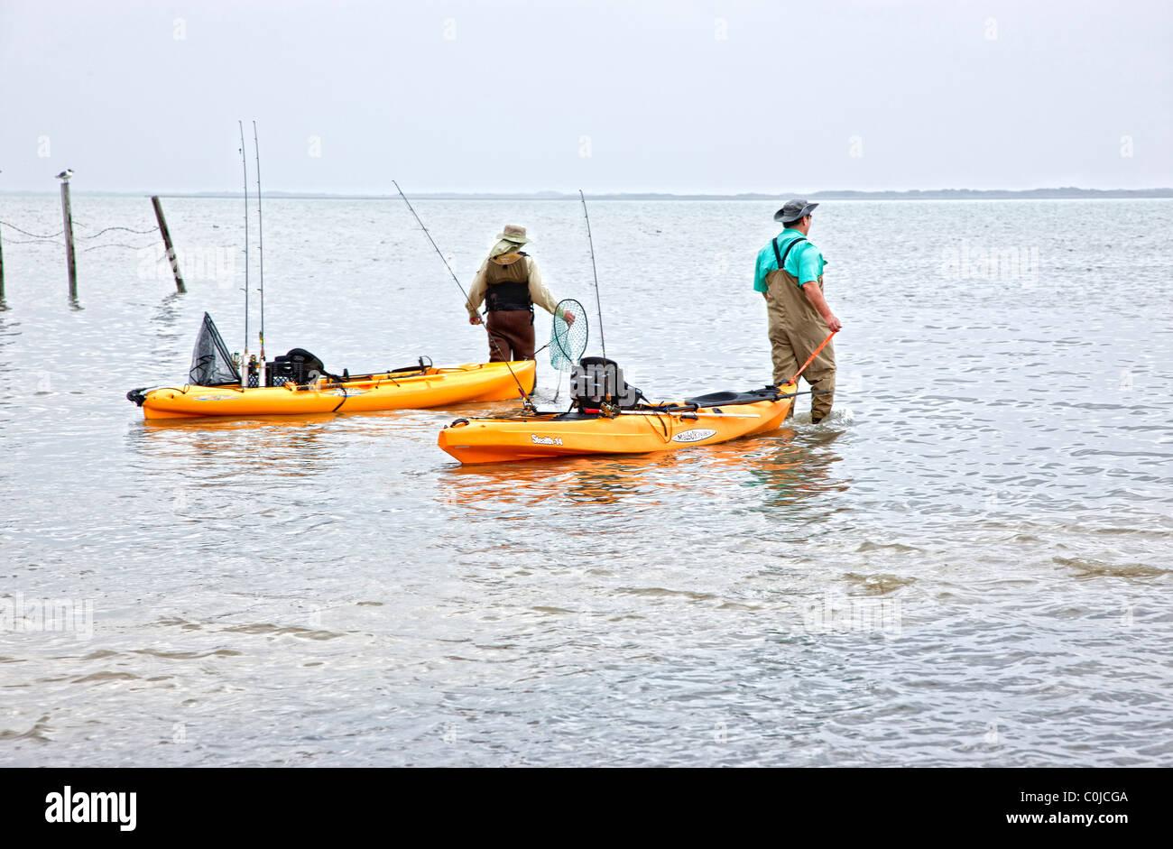 Fishermen launching kayaks, - Stock Image