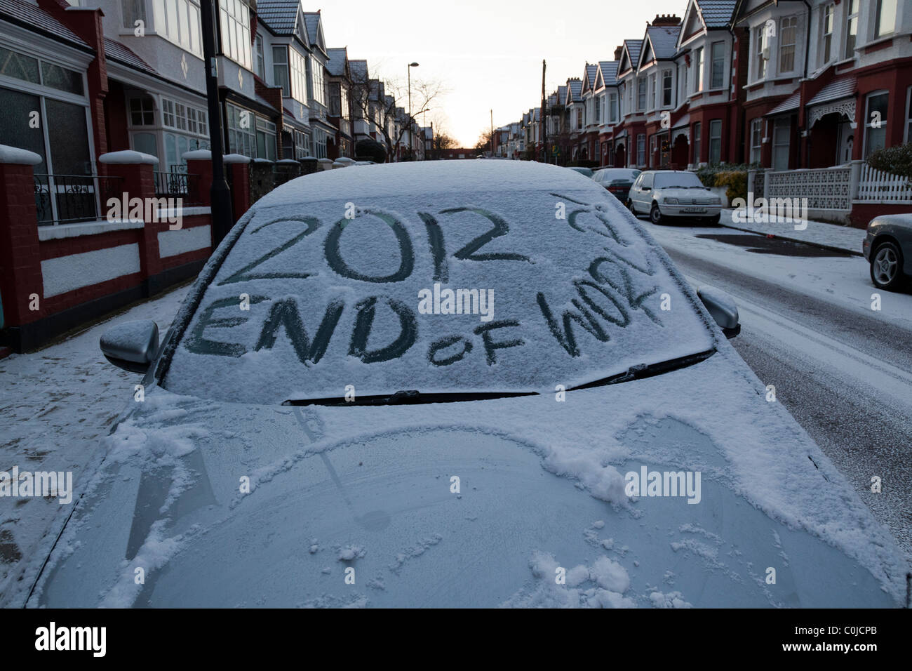 2012 end of the world written on snow-covered car windscreen - Stock Image