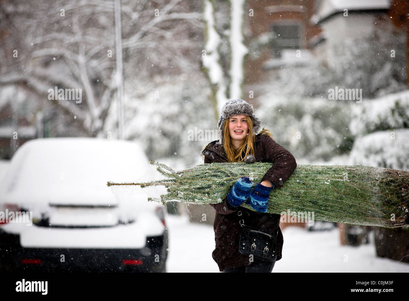A young woman carrying a Christmas tree along a snowy street Stock Photo