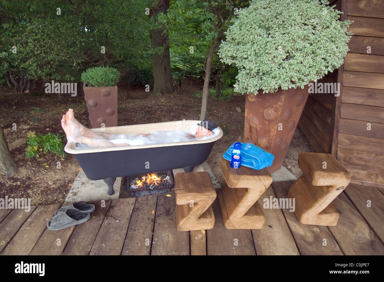 Man relaxing in his coal fired outdoor bathtub by his cabin in the woods. - Stock Image