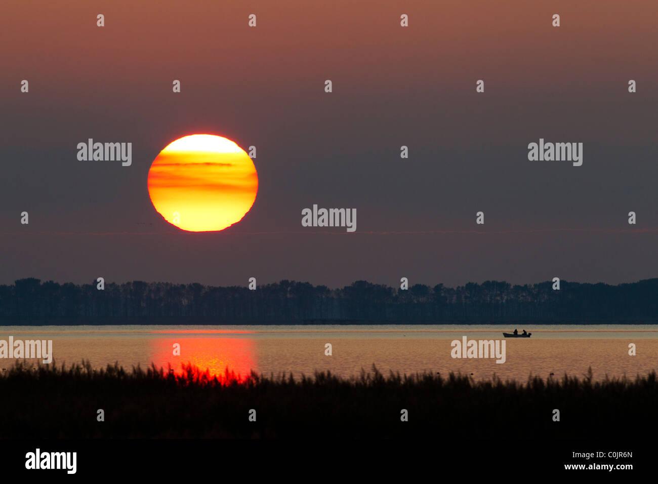 Fishermen in rowing-boat on lake at sunset, Western Pomerania, Germany - Stock Image