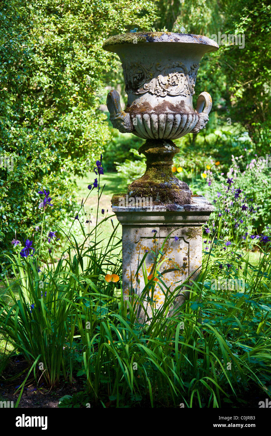 An ornamental stone urn on a plinth in an English country garden. - Stock Image