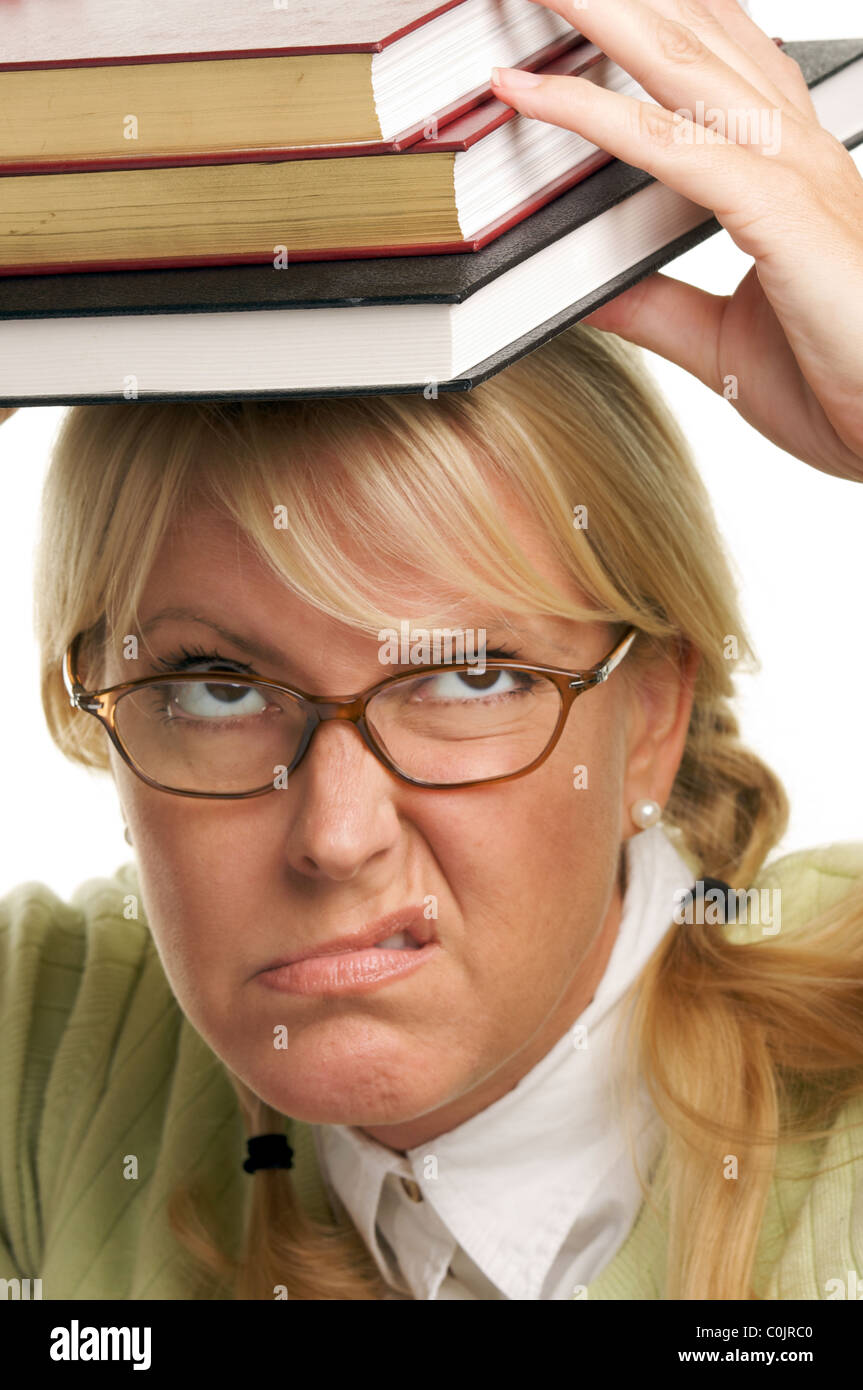 Disgruntled Student with Books Piled on her Head Isolated on a White Background. - Stock Image