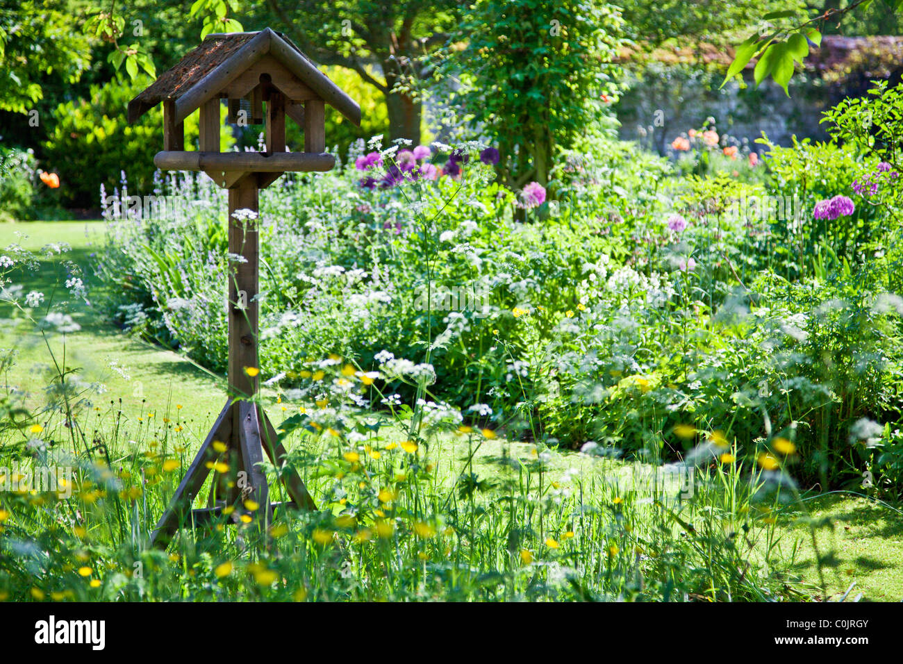 A Pretty Rustic Wooden Bird Table Set Amongst Flower Borders Or