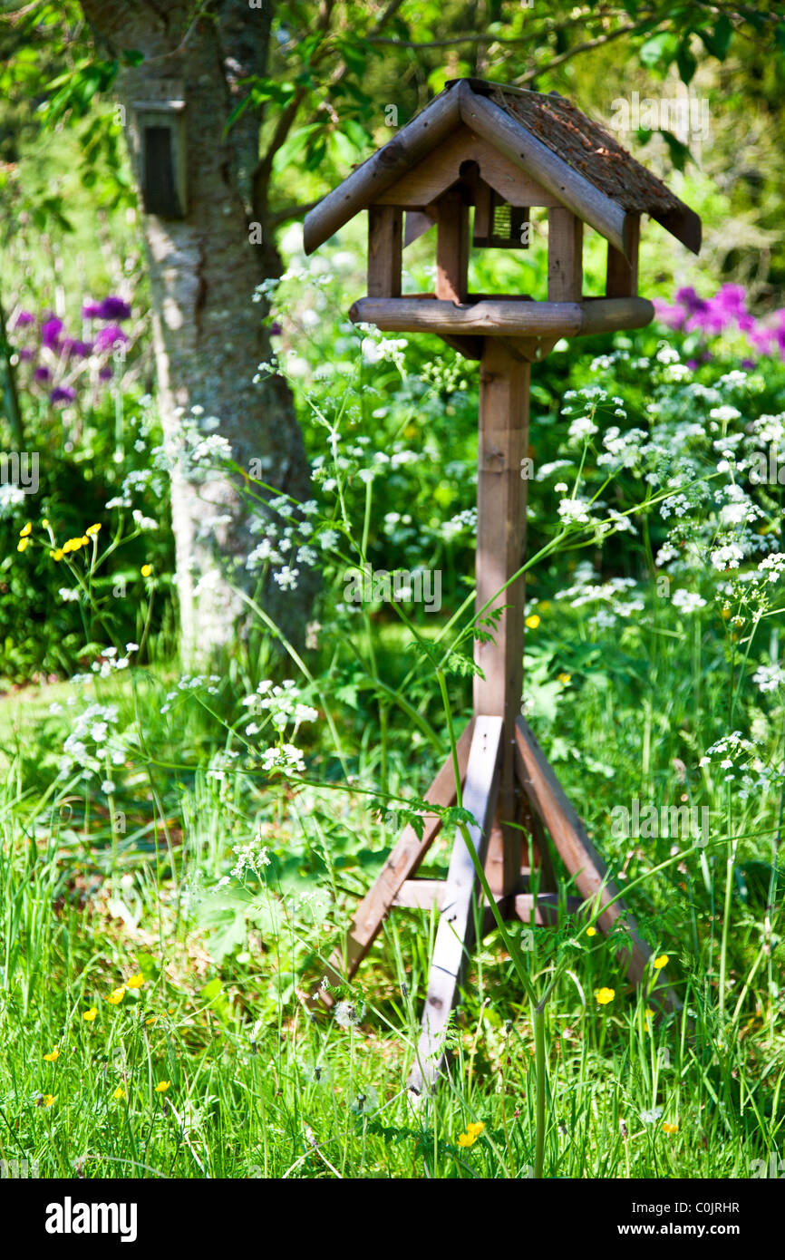 A Pretty Rustic Wooden Bird Table Or Feeder Set Amongst Flower