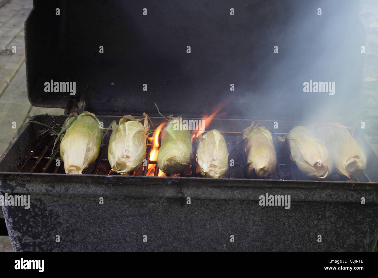 Summer treat, sweet corn ears roasting on the charcoal grill - Stock Image