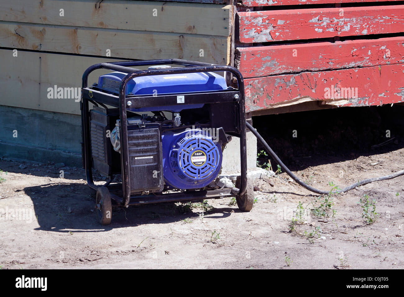 Portable generator being used at remote farm building - Stock Image