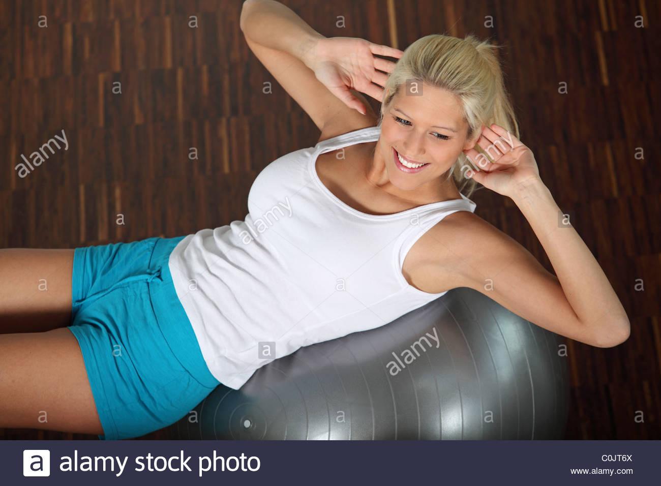 blond woman doing gymnastics on the floor - Stock Image