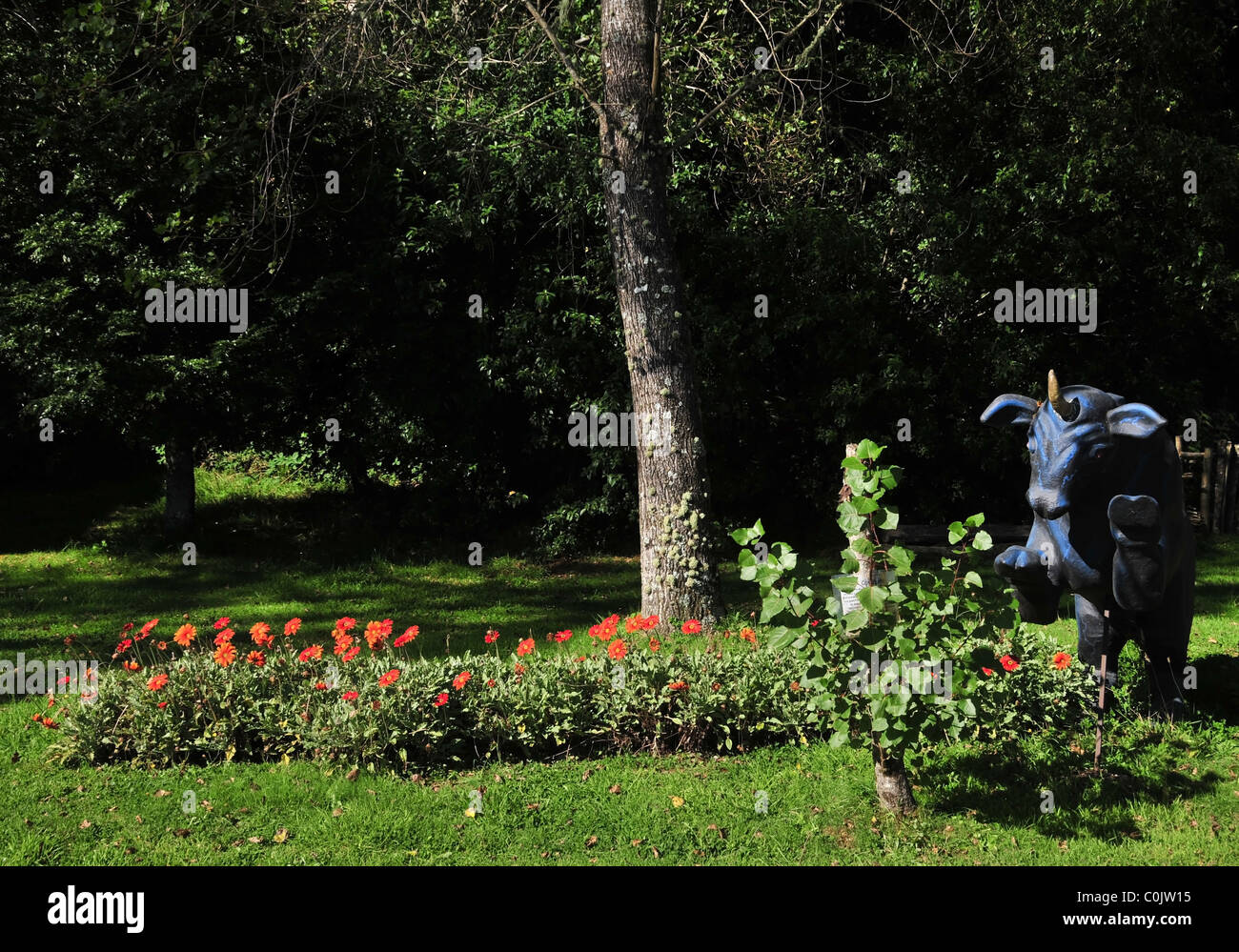 Sunny garden view, with red flowers, grass, trees and blue Camahueto bull-unicorn effigy , Caulin, Chiloe Island, Stock Photo