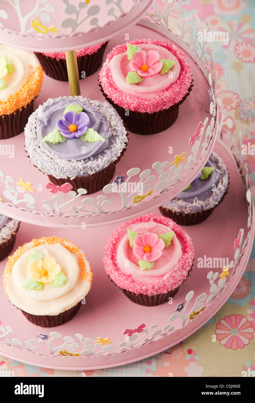 pink yellow purple coloured cup cakes on stand - Stock Image