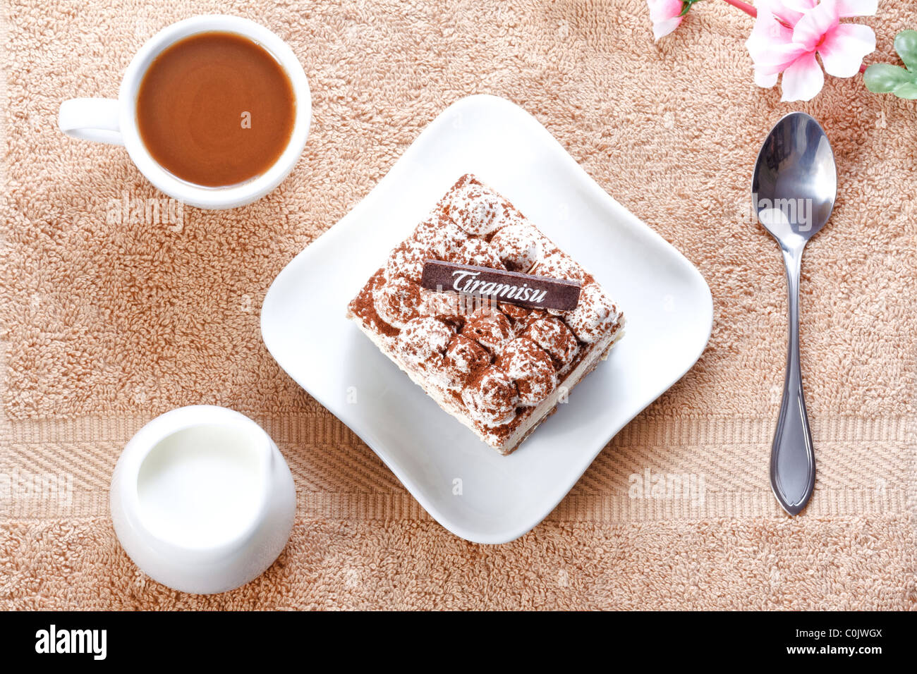 Portion of tiramisu dessert served on a white shaped plate and a cup of coffee with cream - Stock Image