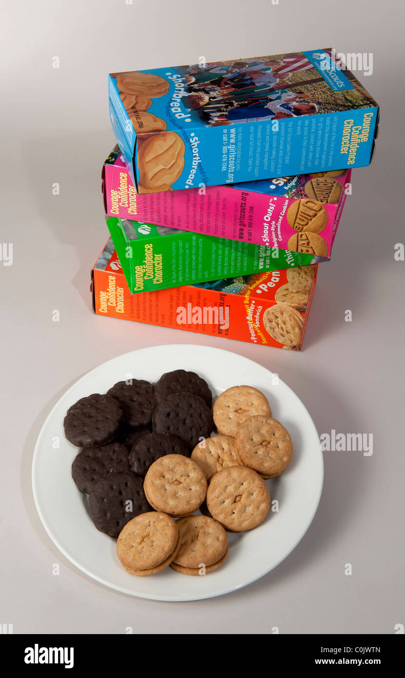 Girl Scout cookies on a dish with boxes in the background - Stock Image