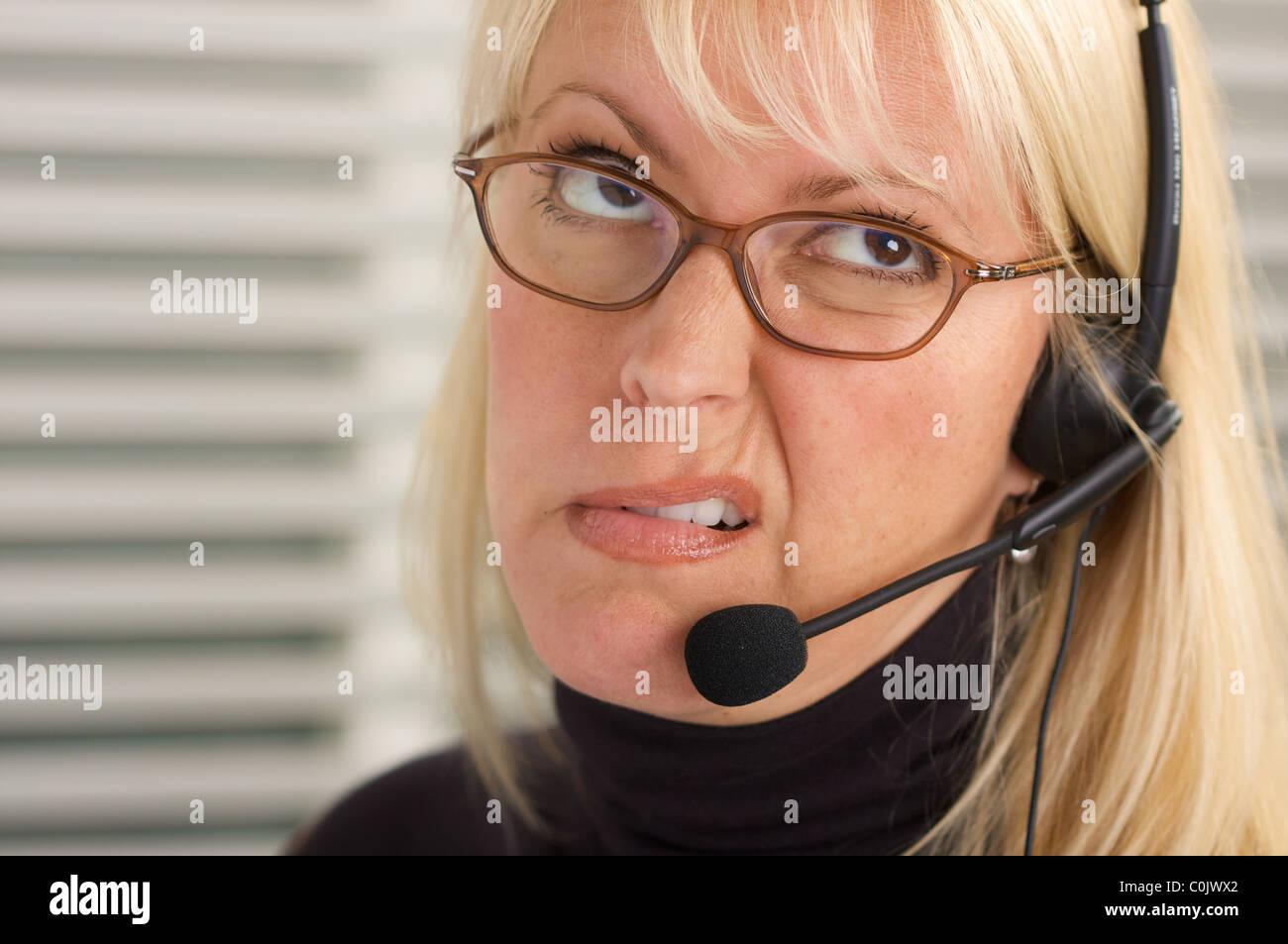 Disgruntled businesswoman talks on her phone headset. - Stock Image