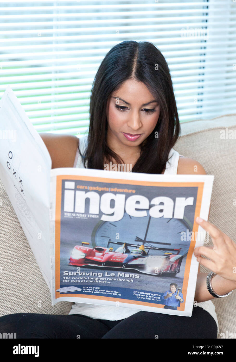 young woman reading motoring magazine supplement in UK - Stock Image
