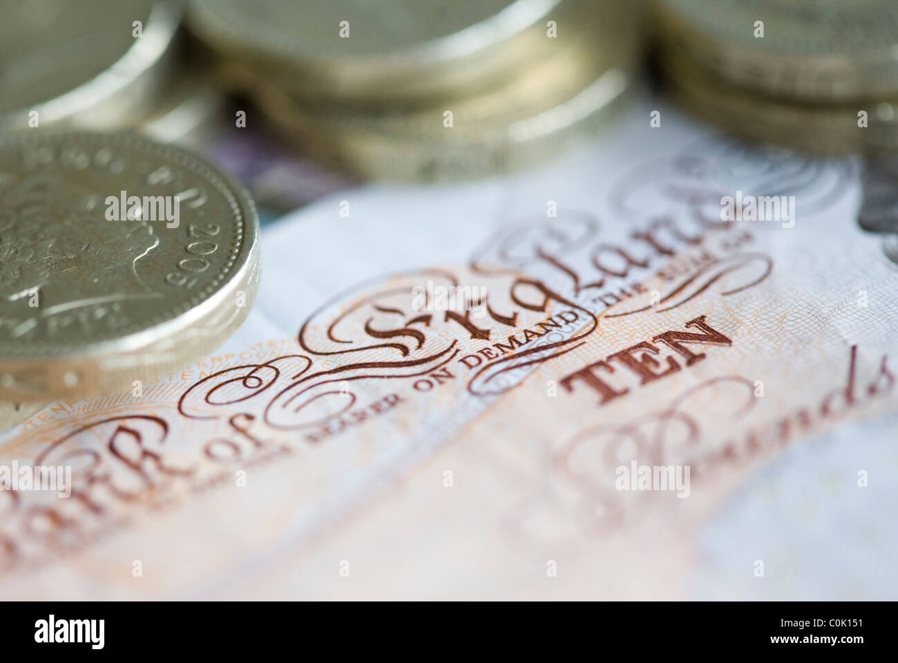 Ten pound sterling notes and one pound coins are set up for a photograph - Stock Image