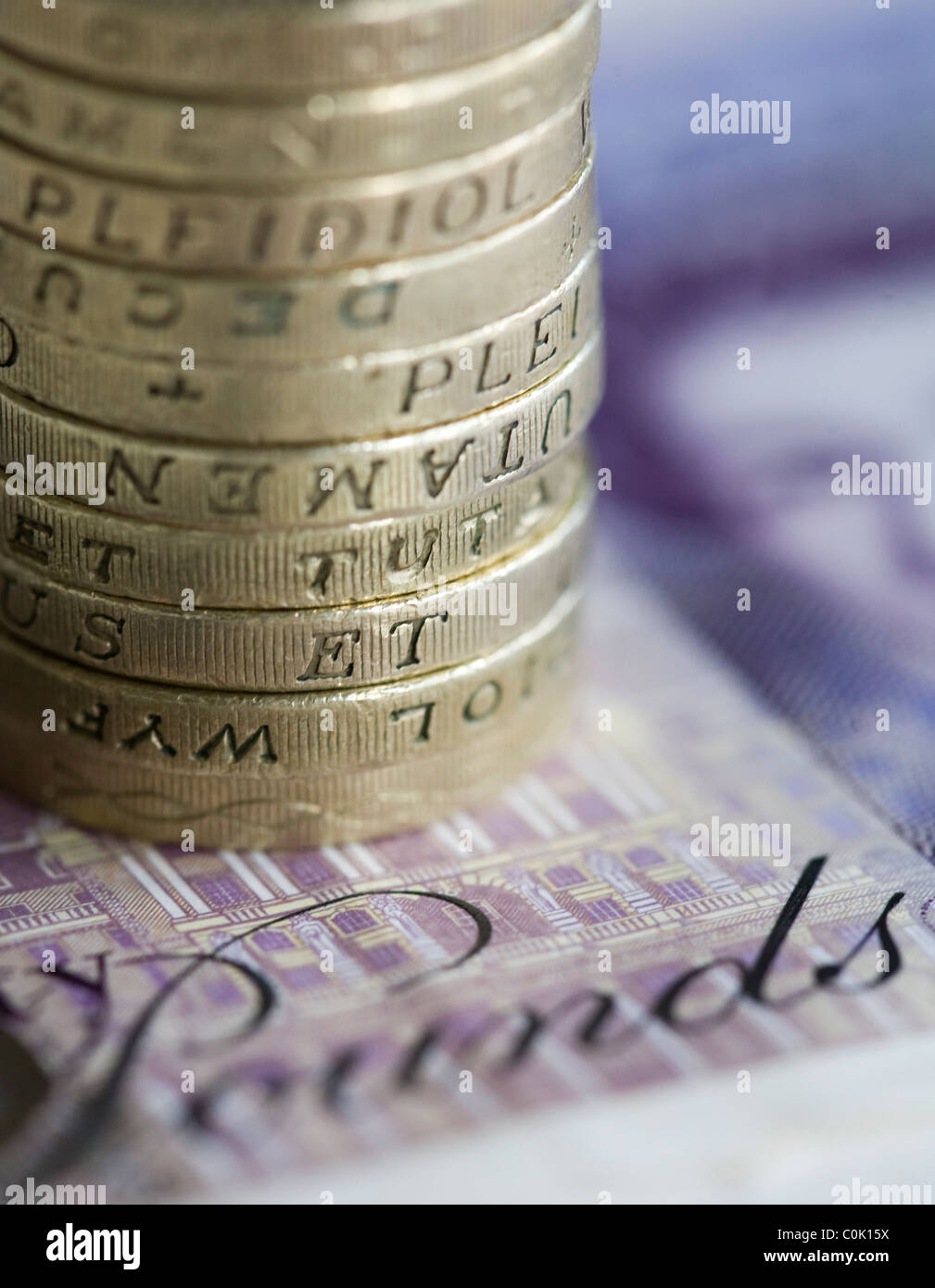 Twenty pound sterling notes and one pound coins are set up for a photograph - Stock Image