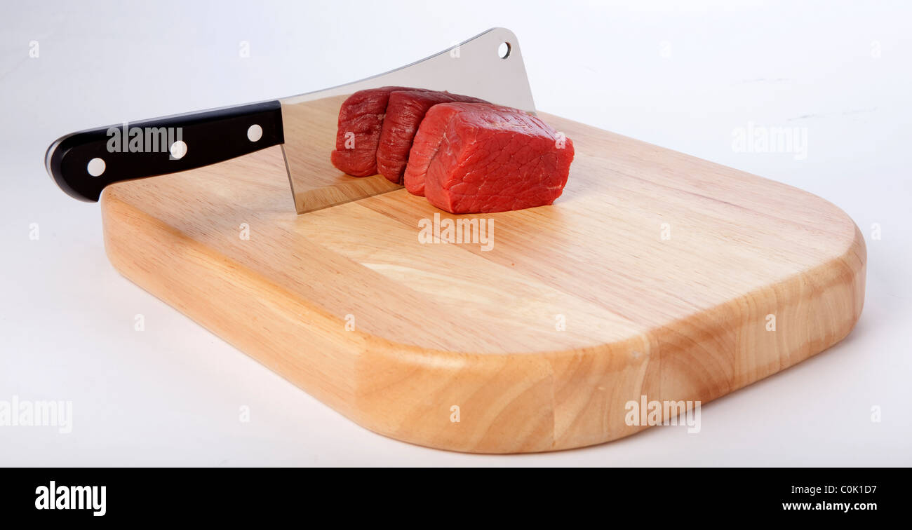 Meat cleaver on a chopping board - Stock Image