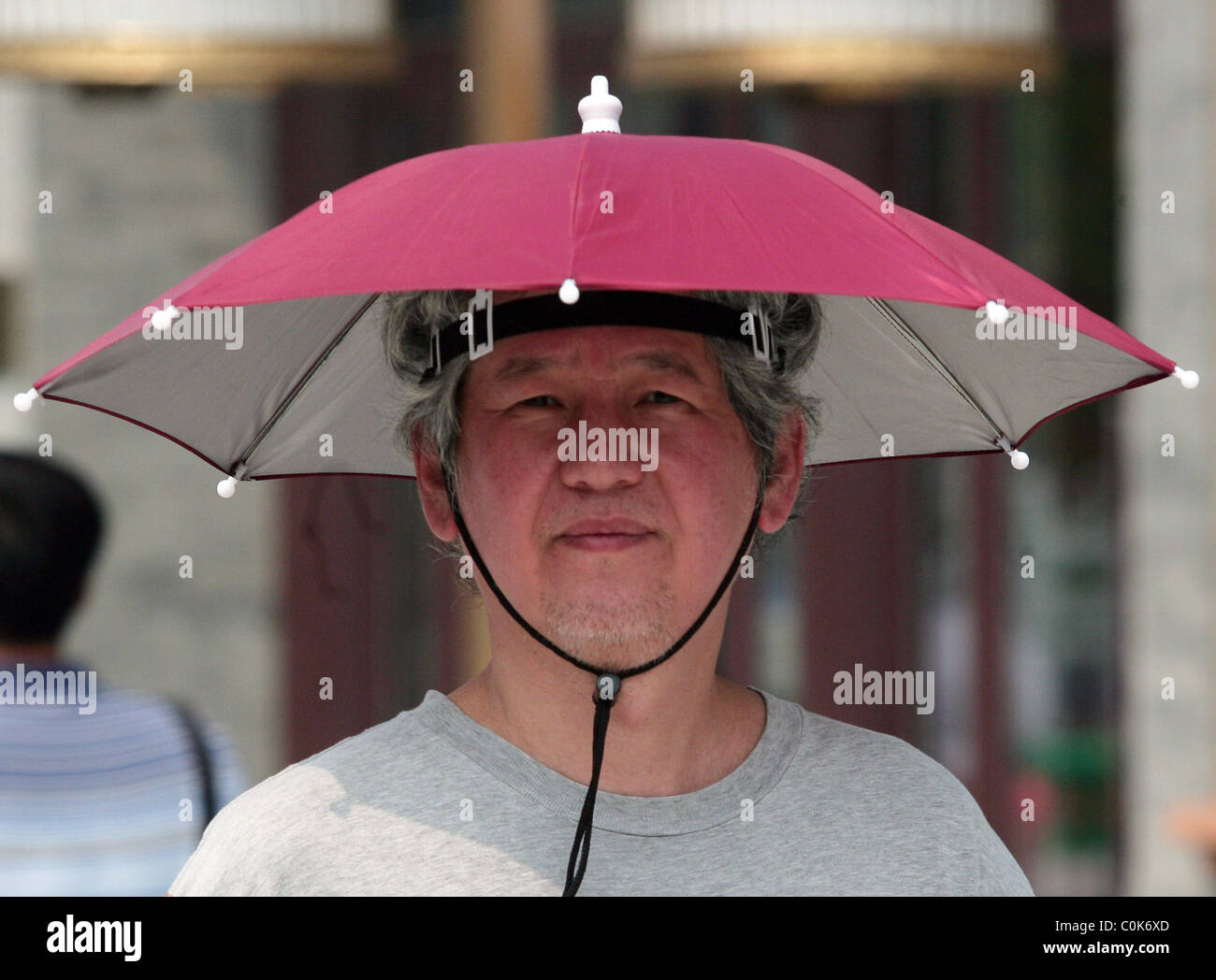 4e8e93614 An elderly lady wears an umbrella hat to protect against the hot sun ...