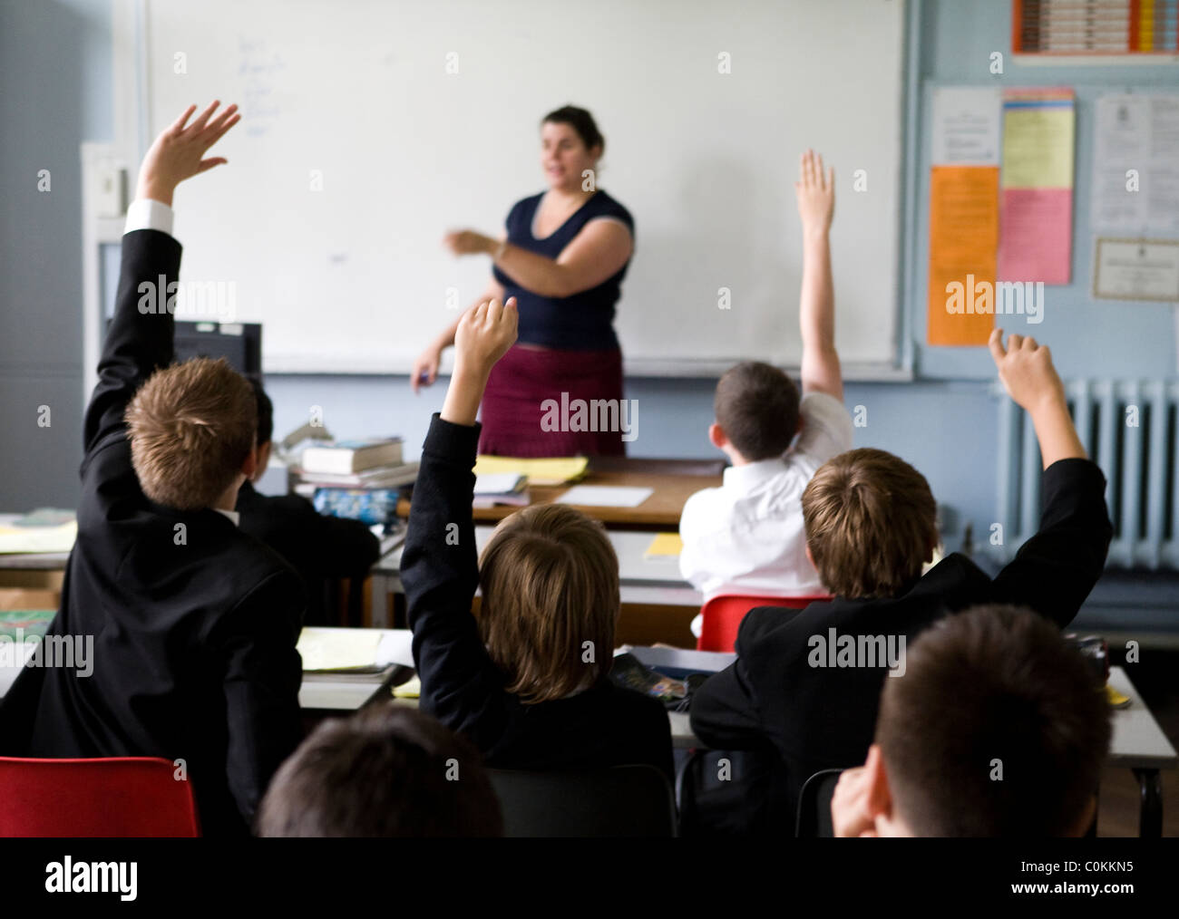Pupils put up their hands to answer a questions at Maidstone Grammar school in Maidstone, Kent, U.K. - Stock Image