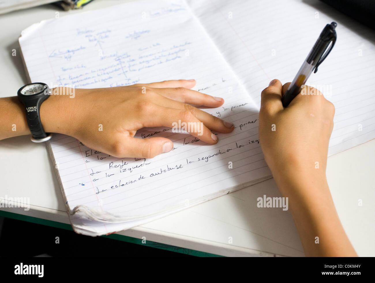 A pupil fills in a textbook at Maidstone Grammar school in Maidstone, Kent, U.K. - Stock Image