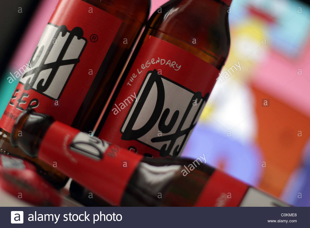 Duff Beer bottles stand in front of a screen playing the Matt Groening cartoon 'The Simpsons'. - Stock Image